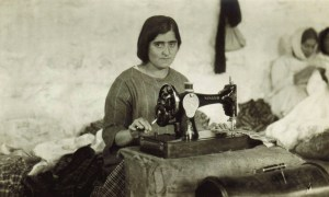 A young woman sews on a Singer sewing machine. Girls also learned dressmaking and hand-sewing.