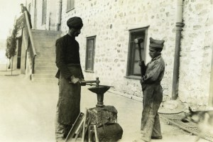 A man and boy practice smithing outdoors.