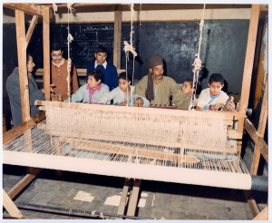 A man teaches a group of young boys to weave on a large loom in Egypt.