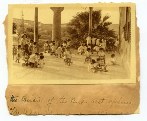 Children from the Birds' Nest playing with toy carts made by boys at Maameltein Orphanage. Includes Nellie Miller's original handwritten caption.