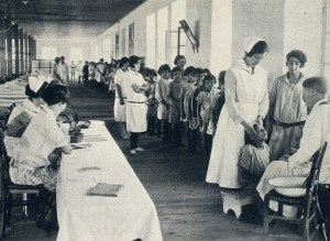 A doctor and three nurses conduct medical examinations in an orphanage hall. Some children received daily medical care, depending upon their health conditions.