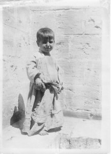 A refugee child in a sack-like dress