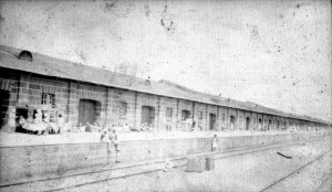 A Garage along train tracks in Kazachi from Jaquith collection. Many people standing on the side of the train tracks with their pieces of luggage and belongings.
