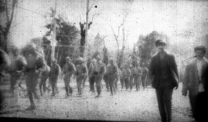 Soldiers walking down a street, date and location unknown. Although the image quality is poor, their rifles are visible.