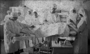 Nurses gather around a patient on table
