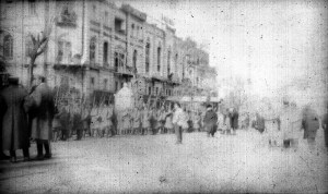Photograph of a city street with soldiers visible in the middle ground. The soldiers are wearing uniforms and carrying rifles. The image is damaged, and the date and location are unknown. It is possible that the soldiers are members of a Greek army battalion either entering or leaving the city of Smyrna.