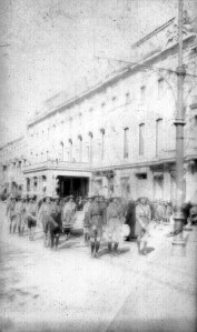 Young men in uniform on a city street in front of a large building. The young men may be dressed as Boy Scouts, or it may be an orphanage uniform. They wear matching shirts, shorts, knee socks, and hats. The boys in the second row appear to be carrying a small trunk. There is a small crowd gathered on the sidewalk, indicating that the boys may be marching in a parade.