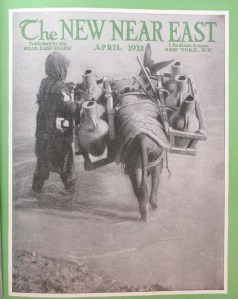 This issue of the New Near East magazine features a stylized image of a young refugee with a laden donkey wading in the water. The location is unknown.
