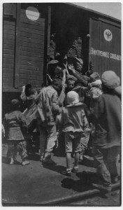 Children raising their hands to soldiers in uniform on a railway car. Children often begged at railway stops. The small child at left has bare feet and extremely ragged clothes. The writing and seal show that this was a Transcaucasian Railway car. H.C. Jaquith's notes identify this as either Batoum or Tiflis, 1920. Both cities were stops on the railway.