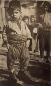 A young boy in traditional costume, including a fez, probably Beirut.