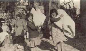 Smiling girls carrying bed rolls outside of an orphanage. This unlabeled photograph is probably from one of the girls' orphanages in Syria that Nellie Miller often visited, such as Seaside (Sidon) or Juniyeh.