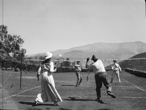 Four people, probably Near East Relief workers or their spouses, playing tennis on a court.