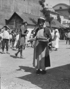 Refugee woman carrying a large bowl.