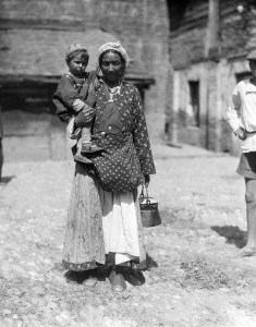 Woman carrying a boy in an embroidered cap and holding a metal pail.