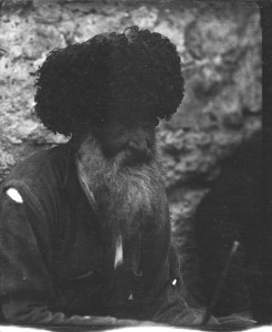 Bearded man with a ripped jacket and a large black hat. The wool hat is typical of the Caucasus region.