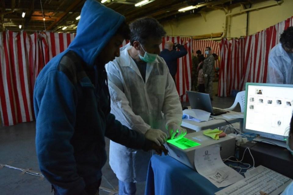 A migrant is fingerprinted onboard the ship San Marco in November 2013. (Polizia di Stato)