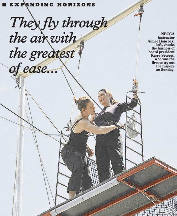 Image of a magazine article with a photo of two people on a flying trapeze rig