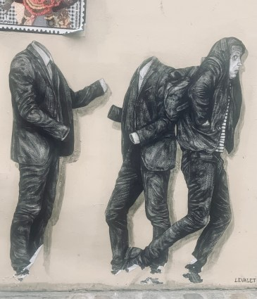 Photo of Paris street art includes a tan building wall on a cobblestone street with the bottom right corner of a multicolored poster in the upper left-hand corner, and a painted black and white image depicting three figures: two formal  suits without bodies facing each other as if engaged in conversation, and a third of a man in casual clothing walking by the other with a frightened look on his face.