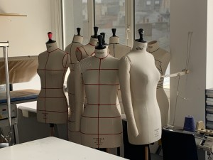 Photo of a cluster of white cloth mannequins, some with taped guide lines for clothing design, in a studio at the Paris College of art. In the foreground is a corner of a sewing table and in the background are various fashion design supplies.
