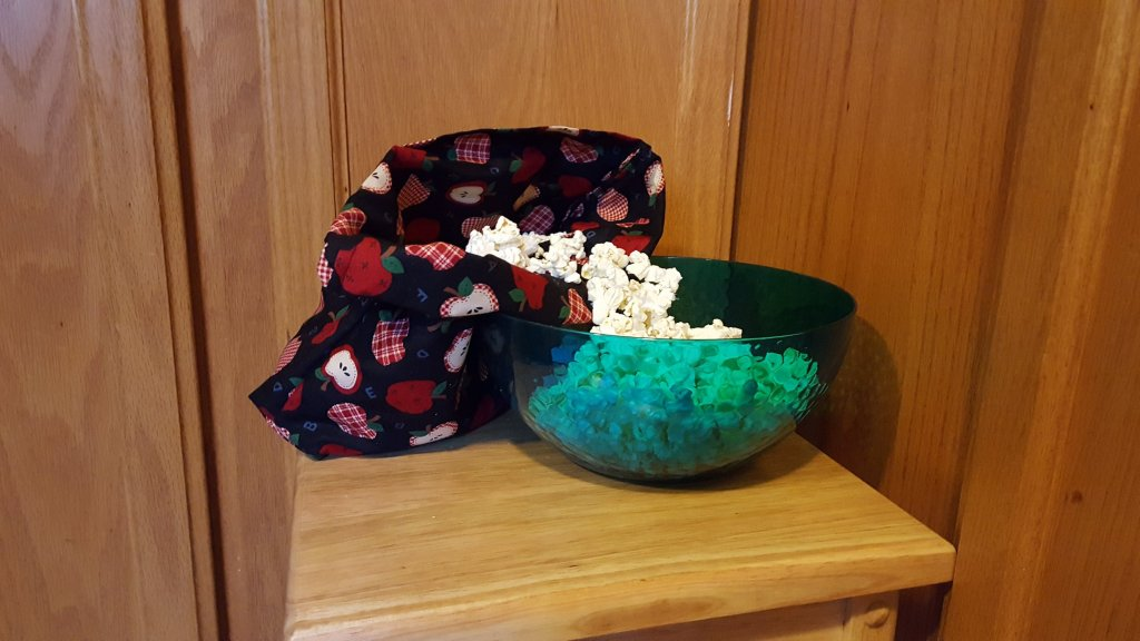 microwave popcorn bag with apple decor on a stool with bowl of popcorn