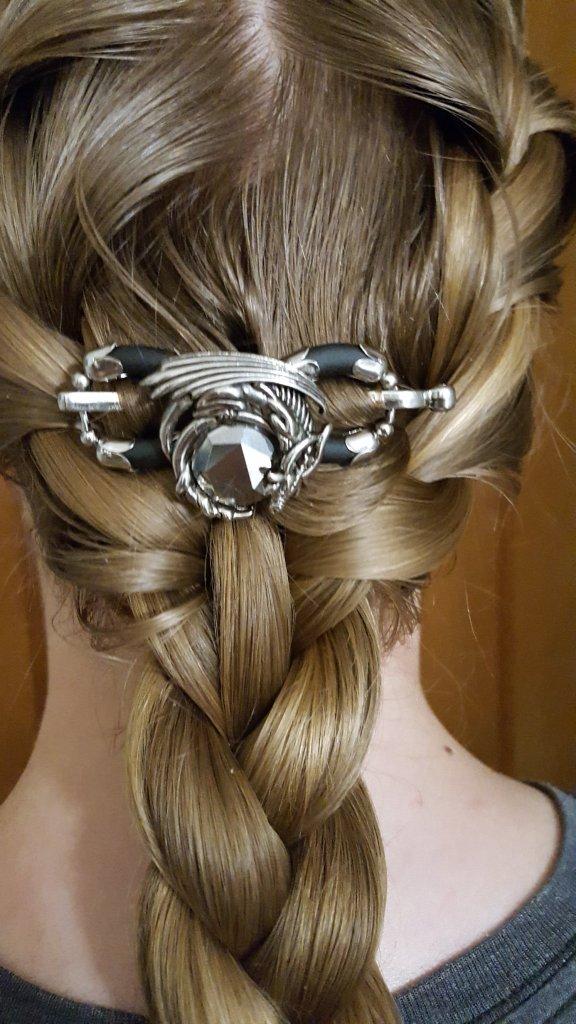 photo close up of a dragon hair clip in a girls hair above a braid