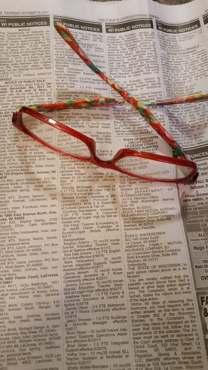 glasses resting on a newspaper with listings of defaulted storage unit auctions