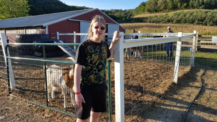 A teen girl wearing glasses with goats shed fence behind her