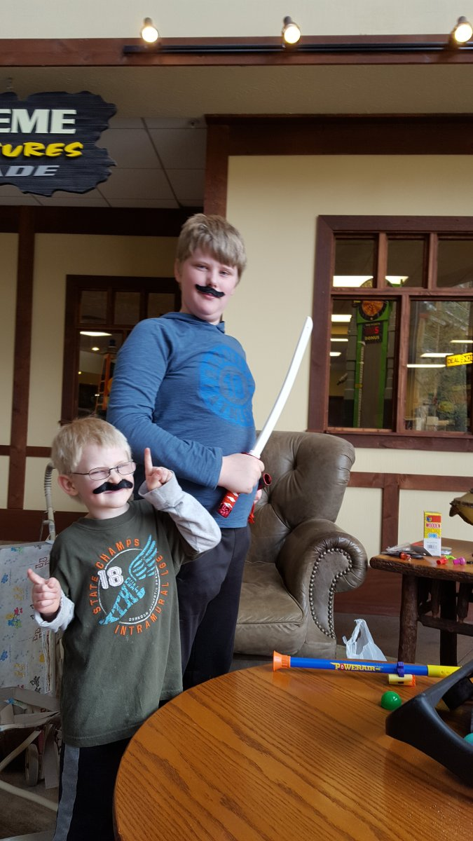 two boys wearing mustaches large family vacation arcade winnings