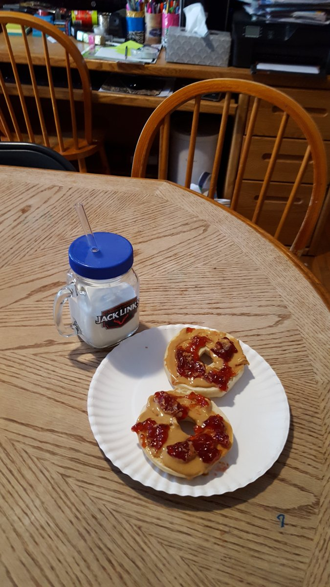 milk in a glass jar with a glass straw and bagels with peanut butter and jelly