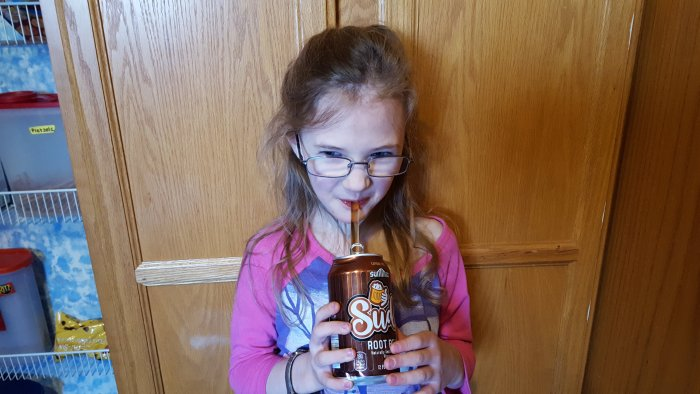 a young girl drinking root beer from a glass straw