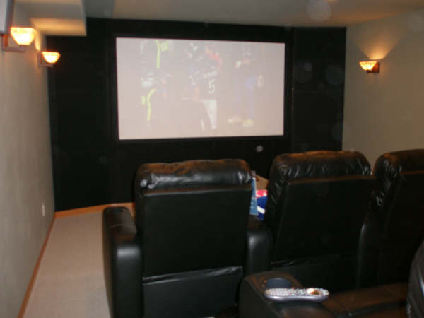 home theater room theater seating in a home with big screen and side lights