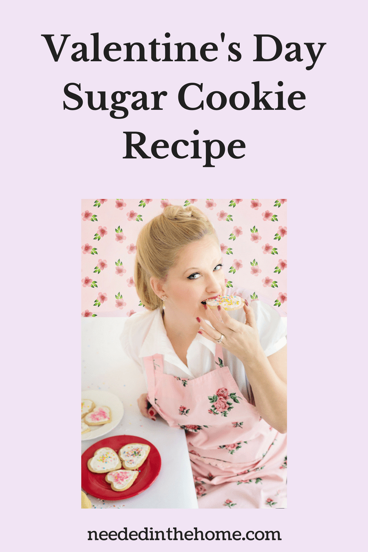 blond woman in an apron biting into a heart shaped frosted sprinkled cookie Valentine's Day Sugar Cookie Recipe neededinthehome.com