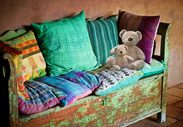 an upcycled antique bench with destressed look painting and pillows and teddy bears