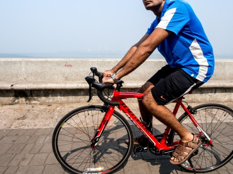 4090: A Cyclist with red cycle on a morning ride. Bicycle is a poor man's transport, hobby of rich man and fitness activity for the everyone.