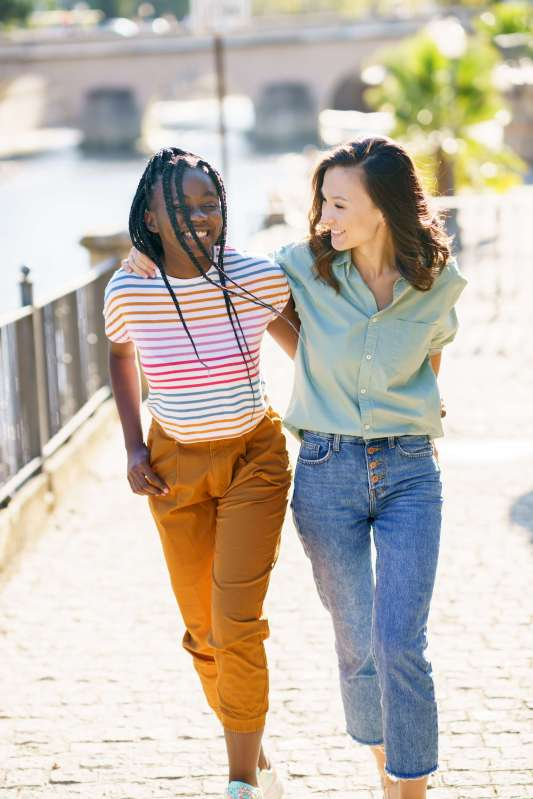 Two friends walking together on the street. Multiethnic women.