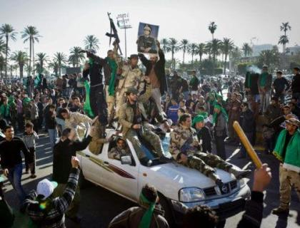 Pro-Gadhafi soldiers and supporters gather in Green Square in Tripoli, Libya Sunday, March 6, 2011. Thousands of Moammar Gadhafi's supporters poured into the streets of Tripoli on Sunday morning, waving flags and firing their guns in the air in the Libyan leader's main stronghold, claiming overnight military successes. (AP Photo/Ben Curtis)