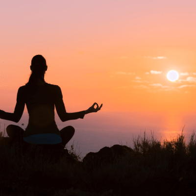 There is a women looking for some peace of mind. It looks like a yoga pose on top of a hill overlooking a sunset.