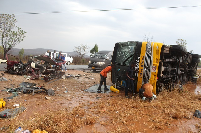 PASSERSBY AT an accident scene where a Mazda Demio was involved in an accident with an Inter Africa bus at Mzingwane High School turn-off in Esigodini yesterday.