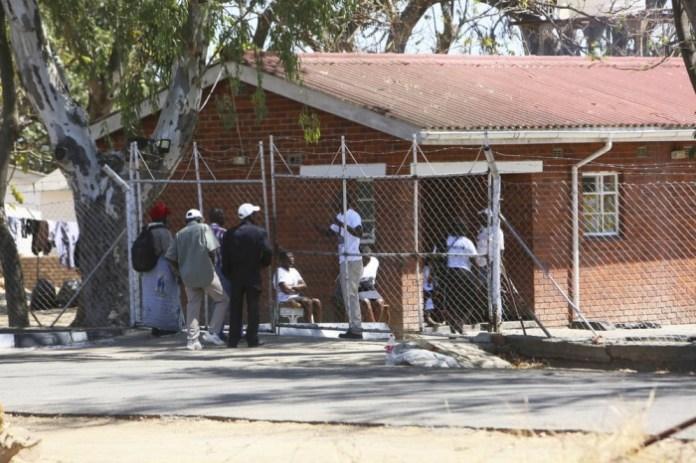 Neighbours negotiate for entrance at the former President Robert Mugabe's rural home in Zvimba, about 100 kilometers north west of the capital Harare, Saturday, Sept. 28, 2019. According to a family spokesperson Mugabe is expected to be buried at the residence after weeks of drama mystery and contention over his burial place. (AP Photo/Tsvangirayi Mukwazhi)