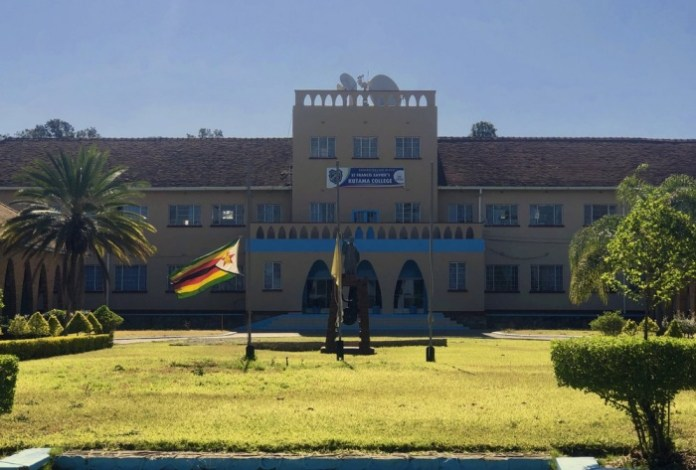 The Zimbabwean flag flies at half mast at Kutama College, a school where former Zimbabwean President Robert Mugabe studied in his rural home in Zvimba about 100 kilometres north west of the capital Harare, Friday, Sept, 27, 2019. Zimbabwe's former presient Robert Mugabe is expected to be buried on Saturday, a family spokesperson said Friday, after three weeks of drama over the former strongman's final resting place.(AP Photo/Tsvangirayi Mukwazhi)