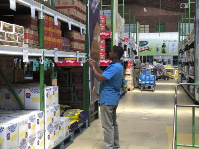 A man takes images of goods in a shop to share before buying them in Harare, in this Wednesday, Oct, 9, 2019 photo. Hyperinflation is changing prices so quickly in the southern African nation that what you would see displayed on a supermarket shelf might change by the time you reach the checkout. (AP Photo/Tsvangirayi Mukwazhi)