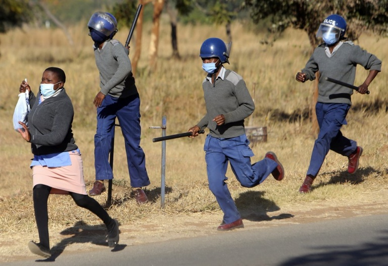 Riot police give chase to nurses who were protesting at a government hospital in Harare, Monday, July, 6, 2020. Thousands of nurses working in public hospitals stopped reporting for work in mid-June, part of frequent work stoppages by health workers who earn less than $50 a month and allege they are forced to work without adequate protective equipment. On Monday, dozens of nurses wearing masks and their white and blue uniforms gathered for protests at some of the country's biggest hospitals in the capital, Harare, and the second-largest city of Bulawayo.(AP Photo/Tsvangirayi Mukwazhi)
