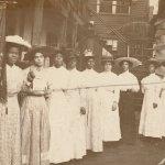 A black and white photo of women in white dresses holding a sign that says Banner State Women's National Baptist Convention. Most of the women are African American, but a few appear to be white.