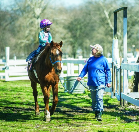 Kylie Fitch, 4, of Dearborn Heights rides Beamer while Edith Abramczyk of Dearborn Heights guides the horse