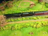 You can see a baseball game behind the model train
