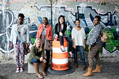 Amy Peterson (seated in front) and Diane Russell (seated on barrel) with the Rebel Nell team: Julia Rhodes, Karen and Patrica, original team members at Rebel Nell, and newer member Eonka Mykira.