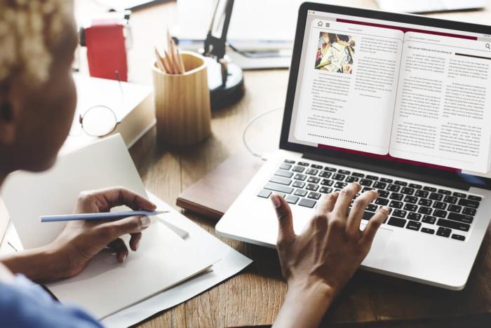 estudante lendo e-book livro digital como produto dinheiro - estudante lendo e book livro digital como produto 700x468 - Como Ganhar Dinheiro na Internet: As 55 Melhores Maneiras (2021)