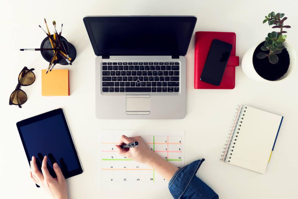 mesa com laptop utennsílios e calendario