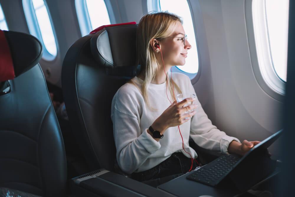 moça acessando laptop no avião