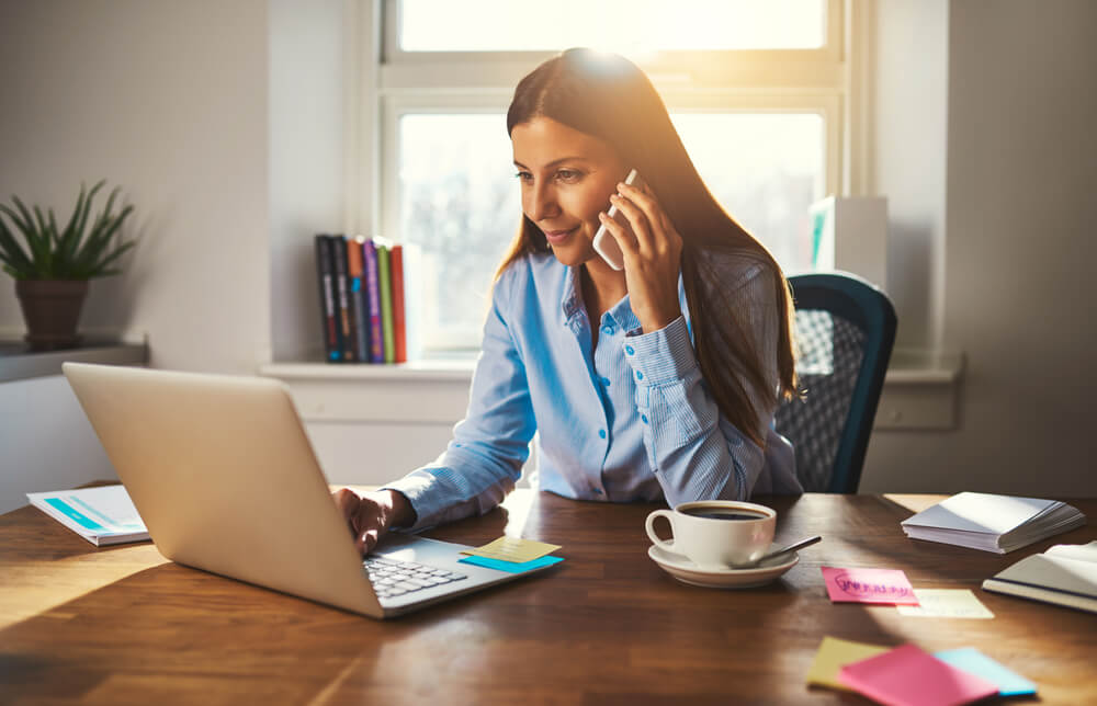 moça jovem trabalhando em home office e falando ao telefone